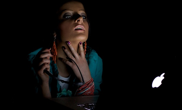 woman_in_a_dark_room_looking_to_a_mac_computer