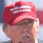 Trump in his signature make america great again hat