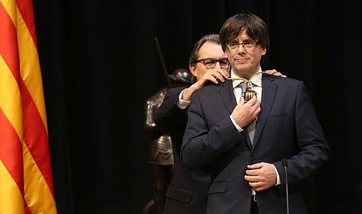 Puigdemont assuming the position of President, in front of his predecessor Artur Mas. (Creative Commons)