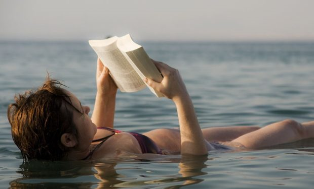 Adult woman reading book in the water